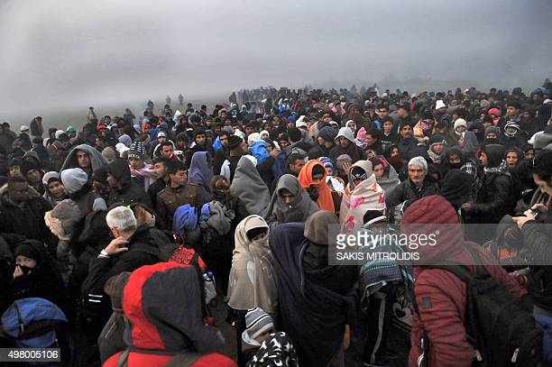 Migrants and refugees wait to cross the GreekMacedonian border near the village of Idomeni on November 20 2015 Countries along the migrant route...