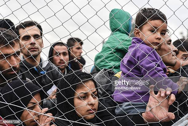 Migrants and refugees wait to cross the GreekMacedonian border near the town of Gevgelija on December 4 2015 Since last week Macedonia has restricted...