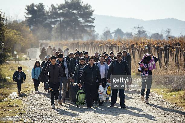 Migrants and refugees walk after crossing the GreekMacedonian border near Gevgelija on November 16 2015 European leaders tried to focus on joint...