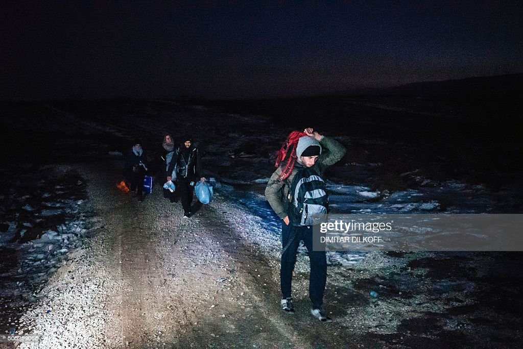 TOPSHOT Migrants and refugees walk after crossing the Macedonian border into Serbia near the village of Miratovac on January 22 2016 Time is running...