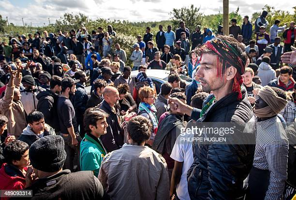 Migrants and refugees walk along with members of a refugee aid organisation as they leave the encampment known as the 'New Jungle' during a...