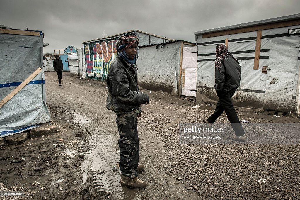 Migrants and refugees walk in the so-called 'Jungle' migrant camp in Calais, northern France. Local French government authorities said on February 12 they want to move up to 1,000 migrants living in the notorious Jungle camp in the port town of Calais. 'The time has come to move on, no one must live in the southern part of the camp, everyone must leave this section,' said Fabienne Buccio, the national's government local representative, estimating some 800 to 1,000 migrants would be affected. / AFP / PHILIPPE HUGUEN