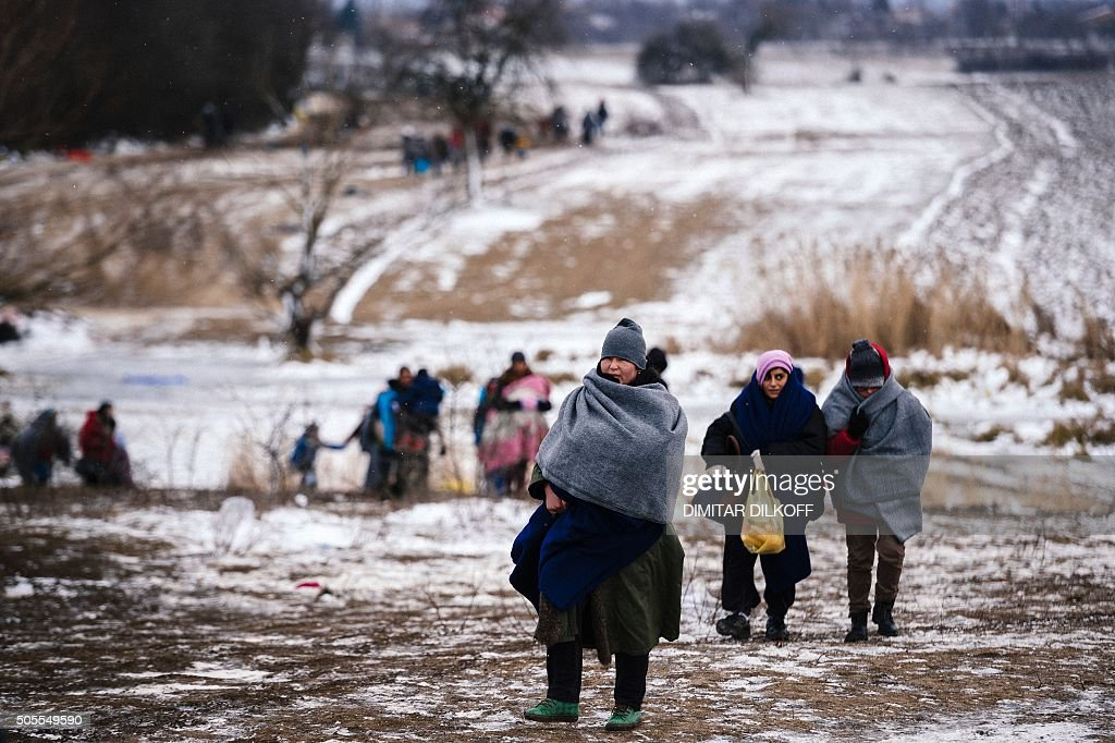 Migrants and refugees walk through snow-covered fields after crossing the Macedonian-Serbian border near the village of Miratovac on January 18, 2016. More than one million migrants reached Europe in 2015, most of them refugees fleeing war and violence in Afghanistan, Iraq and Syria, according to the United Nations refugee agency. / AFP / DIMITAR