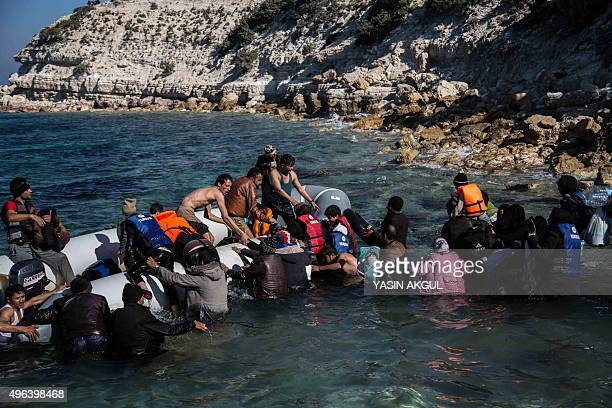 Migrants and refugees walk towards a dinghy to travel to the Greek island of Chios from Cesme in the Turkish province of Izmir on November 9 2015...