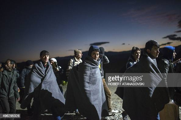 Migrants and refugees wrapped in blankets queue to enter a registration camp after crossing the GreekMacedonian border near Gevgelija on November 8...