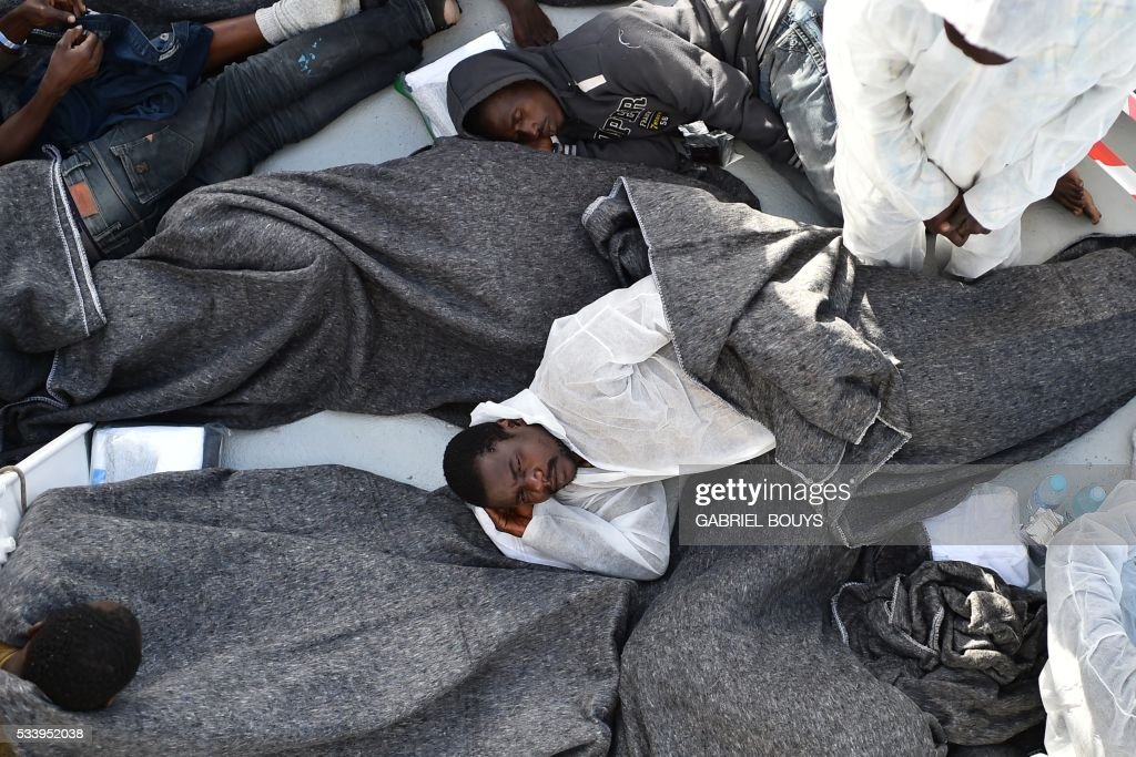 Migrants and refugees wrapped in blankets rest aboard the 'Aquarius', a ship rented by humanitarians SOS Mediterranee and Medecins Sans Frontieres (Doctors without Borders) to organise rescue operations at sea, on May 24, 2016 in front of the Libyan coast. The 'Aquarius' patrols to rescue migrants and refugees trying to reach Europe crossing the Mediterranean sea aboard rubber boats or old fishing boat. / AFP / GABRIEL