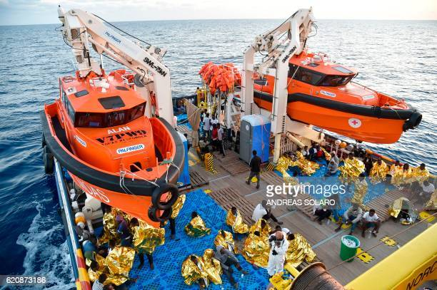 TOPSHOT Migrants and refugees wrapped in survival foil blankets rest aboard the Topaz Responder ship run by Maltese NGO Moas and the Italian Red...