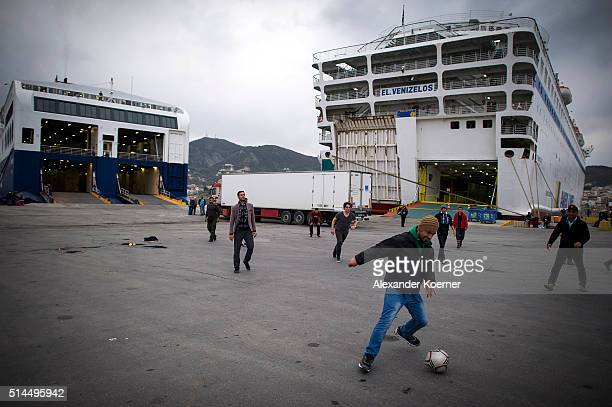Migrants and refugess play football inside the Port of Mytelene prior boarding a ferry which will bring 500 refugees to Athens on March 9 2016 in...