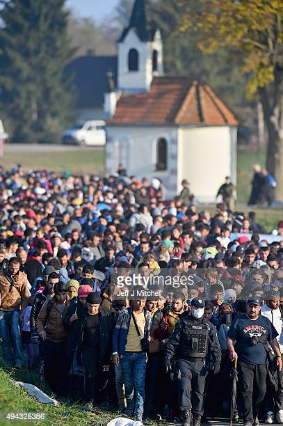 Migrants are escorted by police through fields towards a holding camp in the village of Dobova on October 26 2015 in Rigonce Slovenia Thousands of...