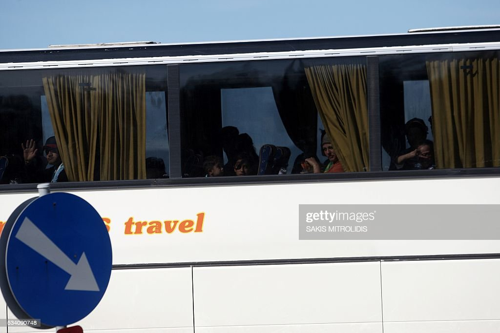 Migrants are evacuated by bus from the makeshift camp near the Greek-Macedonian border in Idomeni on 25 May, 2016. In an operation which began shortly after sunrise on May 24, hundreds of Greek police began evacuating the sprawling camp which is currently home to 8,400 refugees and migrants, among them many families with children, an AFP correspondent said. At its height, there were more than 12,000 people crammed into the site, many of them fleeing war, persecution and poverty in the Middle East and Asia, with the camp exploding in size since Balkan states began closing their borders in mid February in a bid to stem the human tide seeking passage to northern Europe. / AFP / SAKIS