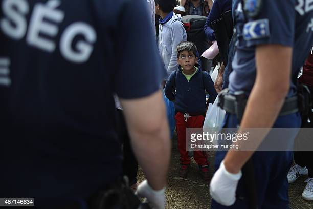 Migrants are greeted by Hungarian police after crossing the border from Serbia into Hungary along the railway tracks close to the village of Roszke...