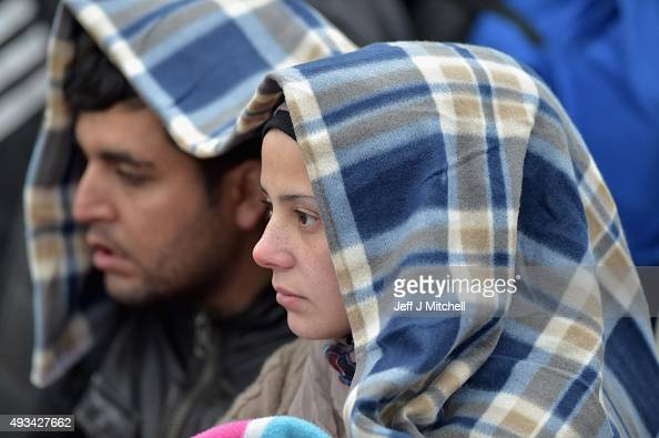 Migrants are wrapped in blankets as they wait in the field near the crossing border between Serbia and Croatia on October 20 2015 near the village of...