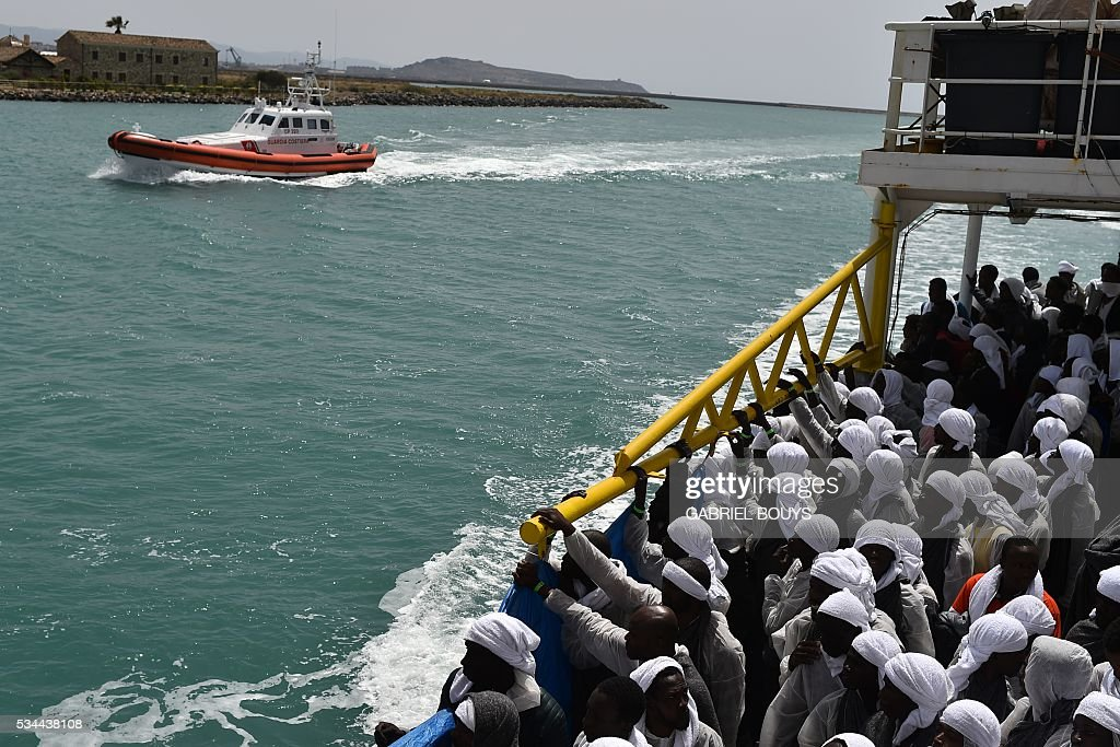 Migrants arrive in the port of Cagliari, Sardinia, aboard rescue ship 'Aquarius', on May 26, 2016, two days after being rescued near the Libyan coasts. The Aquarius is a former North Atlantic fisheries protection ship now used by humanitarians SOS Mediterranee and Medecins Sans Frontieres (Doctors without Borders) which patrols to rescue migrants and refugees trying to reach Europe crossing the Mediterranean sea aboard rubber boats or old fishing boat. / AFP / GABRIEL