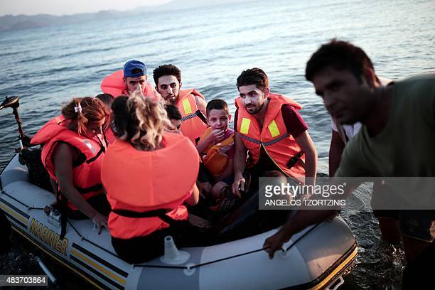 Migrants arrive on a beach on the Greek island of Kos after crossing a part of the Aegean Sea between Turkey and Greece in an inflatable raft on...