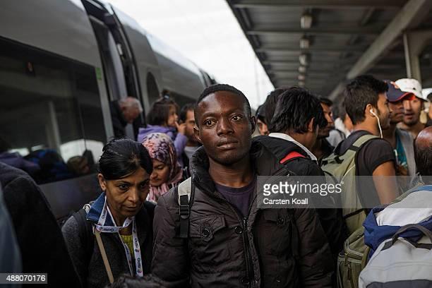 Migrants arrive on an ICE highspeed train of Deutsche Bahn from Munich near Berlin on September 13 2015 in Schoenefeld Germany In an effort to deal...