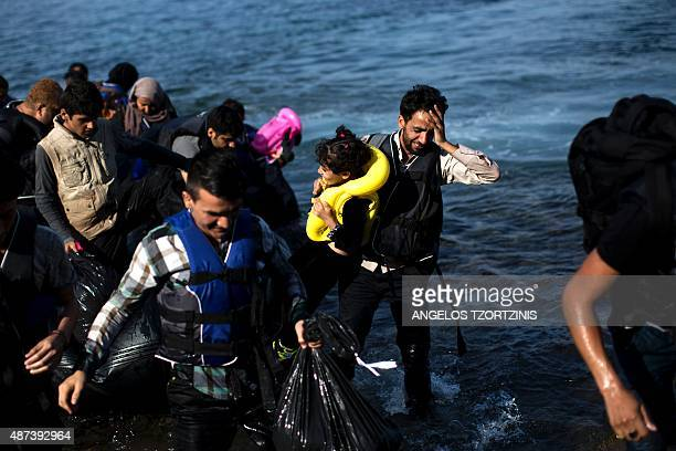 Migrants arrive on the shores of the Greek island of Lesbos after crossing the Aegean Sea from Turkey on a dinghy on September 9 2015 The EU unveiled...