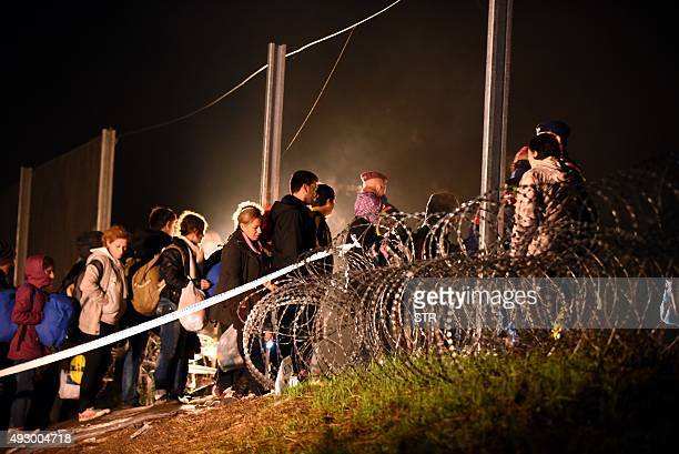 Migrants arriving from Tovarnik cross the border to Hungary before Hungarian police and soldiers closed the border with barbed wire in Botovo on...