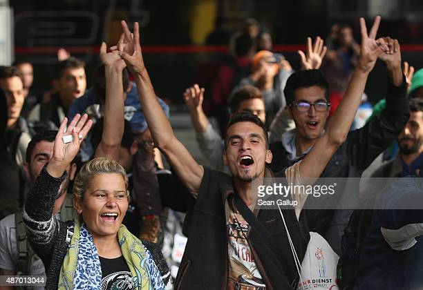 Migrants arriving with approximately 800 others on a train from Hungary react to the welcoming cheers of onlookers at Munich Hauptbahnhof main...