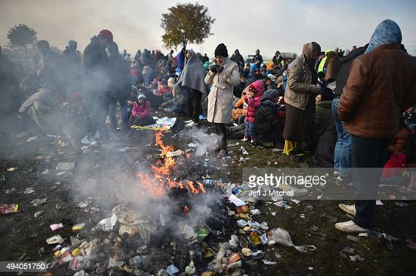 Migrants attempt to keep warm next to a fire as they are held back by the police near the village of Rigonce before being walked to Brezice refugee...