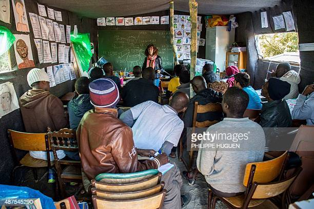 Migrants attend a French class at a makeshift school set up in the 'New Jungle' in Calais northern France on September 10 where more than 3500 people...