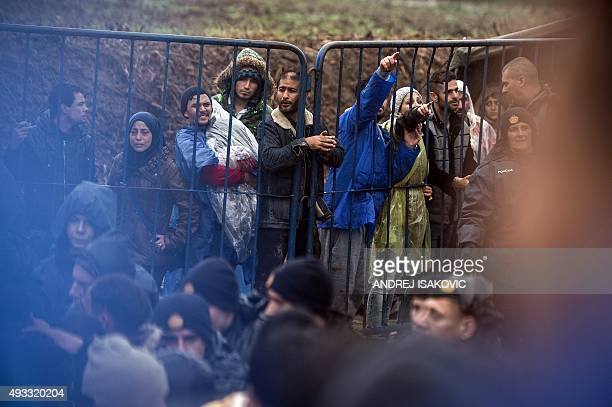 Migrants behind a fence gesture as other migrants wait to enter Croatia from the SerbiaCroatia border near the western Serbian village of Berkasovo...