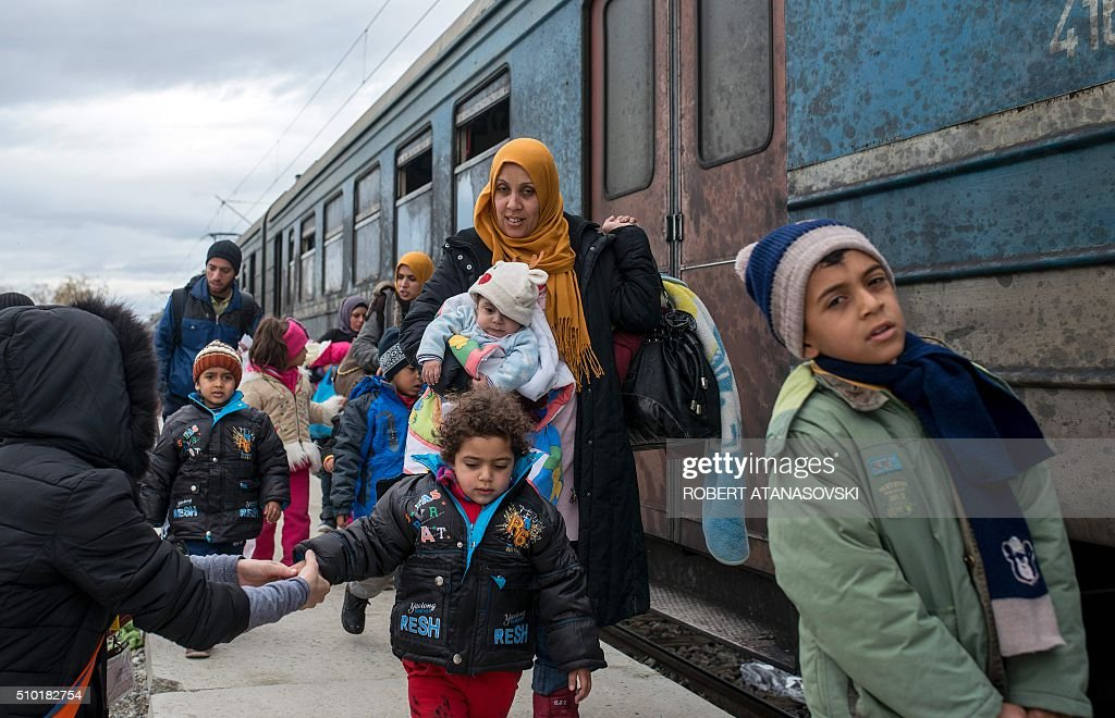 Migrants board a train after crossing the Macedonian-Greek border near Gevgelija on February 14, 2016. Dutch Foreign minister Bert Koenders today spent an hour in a Vinojug recipient center near Gevgelija talking with migrants, children, UNICEF and Red Cross representatives, police and others members that are taking care of migrants that are heading to the EU from devastated homes in Syria, Afghanistan and Iraq. / AFP / Robert ATANASOVSKI