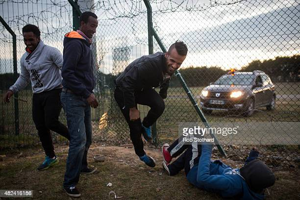 Migrants break through a fence near the Eurotunnel terminal in Coquelles on July 30 2015 in Calais France Hundreds of migrants are continuing to...