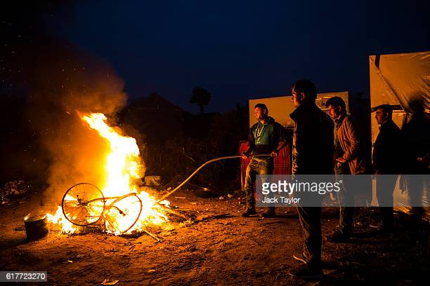 Migrants burn their bikes in a bonfire at the Jungle migrant camp on October 24 2016 in Calais France French authorities have begun to clear the...