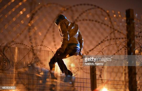 A migrants camped out in Calais attempts to climb a security fence near refugee camp of Calais France on August 3 2015 More than 2 thousands migrants...