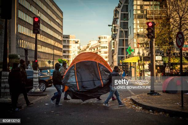 TOPSHOT Migrants carry a tent across a migrant tent camp in Paris on November 3 near to the Stalingrad metro station one of several camps sprouting...