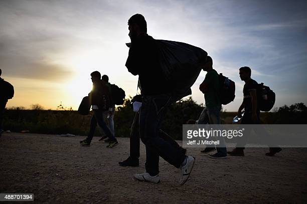 Migrants carry their belongings as they continue to arrive by bus where they will walk the final few kilometres from Serbia to Croatia opening up a...