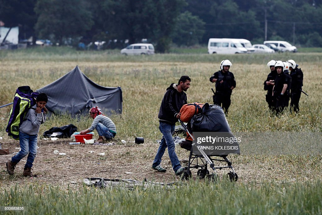 Migrants carry their belongings during an evacuation operation by police forces of a makeshift migrant camp at the border at the Greek-Macedonian border near the village of Idomeni, on May 24, 2016. In an operation which began shortly after sunrise on May 24, hundreds of Greek police began evacuating the sprawling camp which is currently home to 8,400 refugees and migrants, among them many families with children, an AFP correspondent said. At its height, there were more than 12,000 people crammed into the site, many of them fleeing war, persecution and poverty in the Middle East and Asia, with the camp exploding in size since Balkan states began closing their borders in mid February in a bid to stem the human tide seeking passage to northern Europe. / AFP / POOL / YANNIS