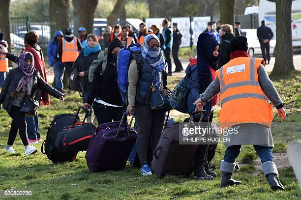 Migrants carry their luggages as they walk to climb into a bus after leaving the 'Jules Ferry' reception centre next to the recently demolished...