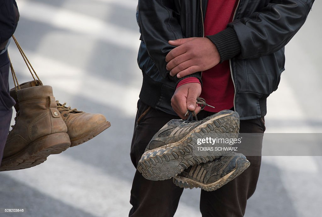 Migrants carry their shoes as they walk on a road after they had been rejected at the Macedonian border towards a makeshift camp for migrants and refugees near the village of Idomeni not far from the Greek-Macedonian border on May 4, 2016. Some 54,000 people, many of them fleeing the war in Syria, have been stranded on Greek territory since the closure of the migrant route through the Balkans in February. / AFP / TOBIAS
