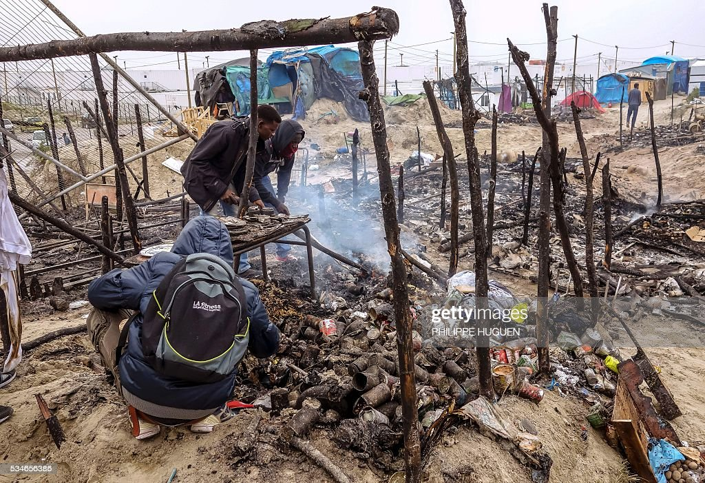 Migrants clean up burnt shelters after a massive brawl that left 40 people injured in the 'Jungle' migrant camp in the northern French town of Calais on May 27, 2016. Some 20 people living in the 'Jungle' refugee camp in the northern French port of Calais were injured in a brawl between around 200 Afghans and Sudanese on May 26, 2016. / AFP / PHILIPPE