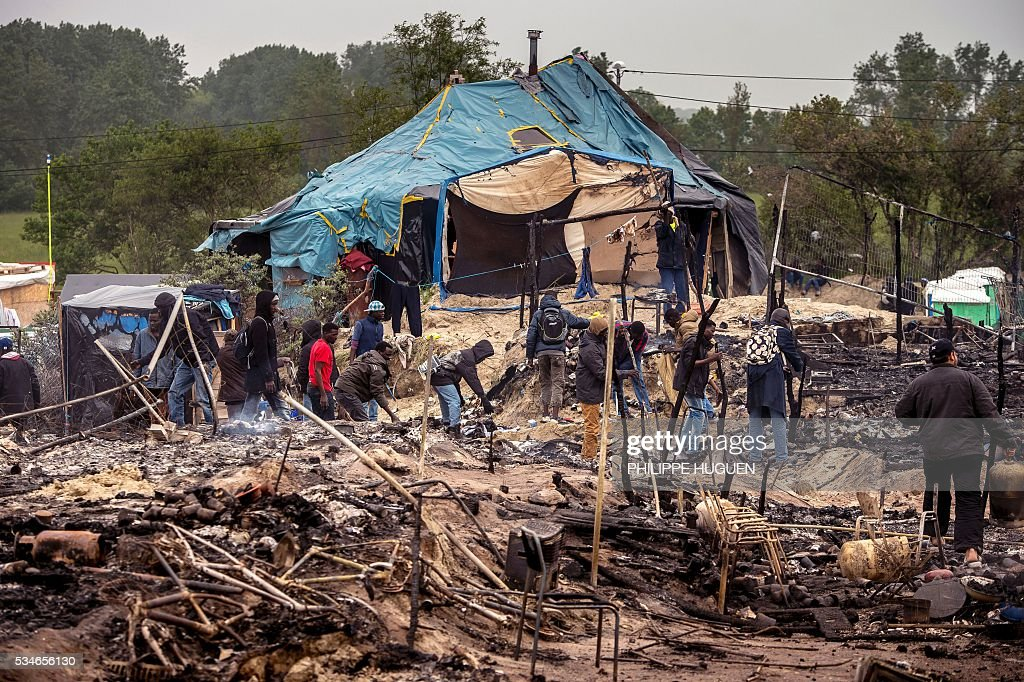 Migrants clean up burnt tents after a massive brawl that left 40 people injured in the 'Jungle' migrant camp in the northern French town of Calais on May 27, 2016. Some 20 people living in the 'Jungle' refugee camp in the northern French port of Calais were injured in a brawl between around 200 Afghans and Sudanese on May 26, 2016. / AFP / PHILIPPE