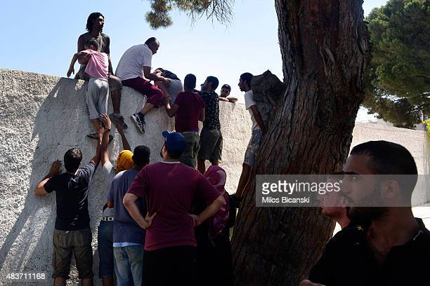 Migrants climb a wall of the national stadium where a registration exercise for the migrants is taking place on August 12 2015 in Kos Greece Greek...