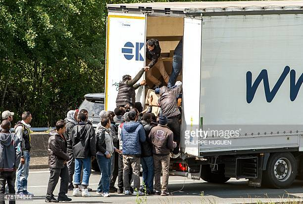 Migrants climb in the back of a lorry on the A16 highway leading to the Eurotunnel on June 23 2015 in Calais northern France Some of the thousands of...