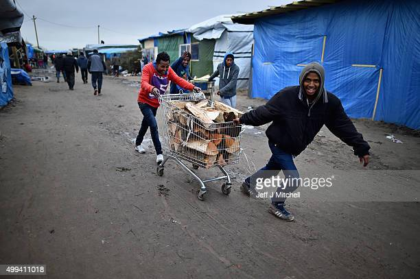 Migrants collect wood as they contend with wintery conditions in the camp known as the 'New Jungle' on December 1 2015 in Calais France Thousands of...