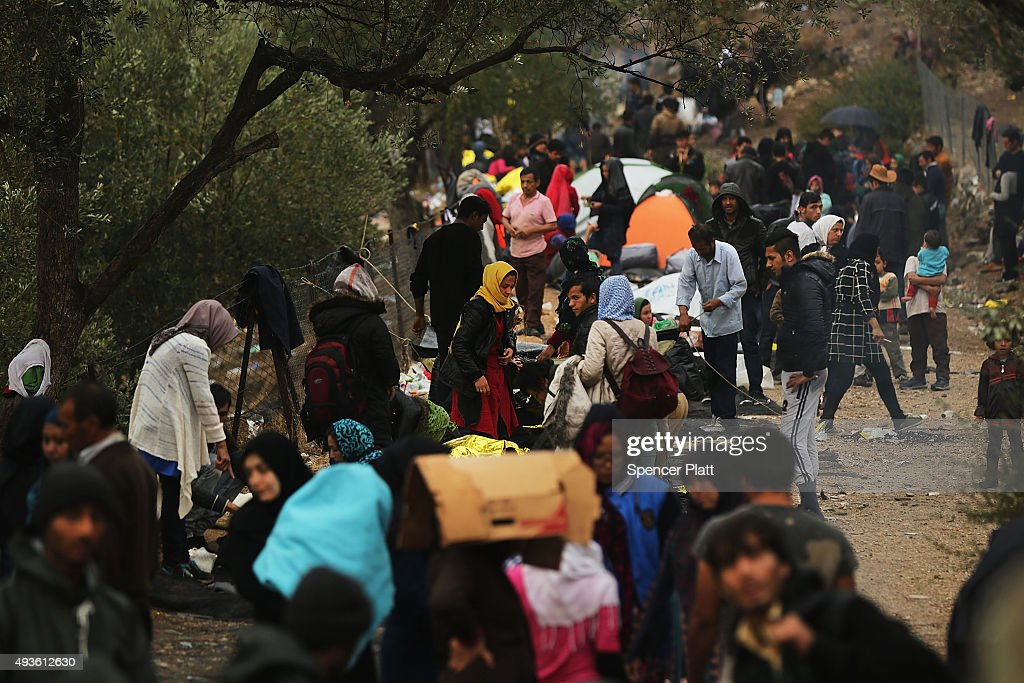 Migrants cope with the wet and cool weather while waiting to be processed at the increasingly overwhelmed Moria camp on the island of Lesbos on...