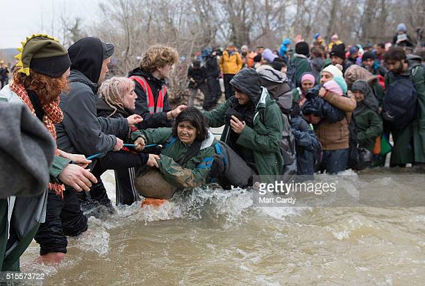 Migrants cross a river after leaving the Idomeni refugee camp on March 14 2016 in Idomeni Greece The decision by Macedonia to close its border to...