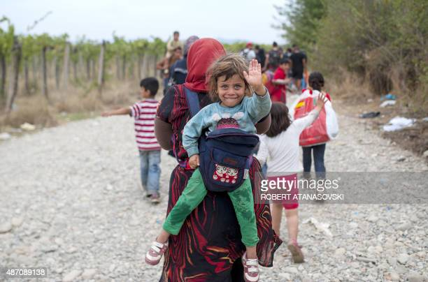 Migrants cross the border line between Greece and Macedonia near the town of Gevgelija on September 6 2015 Some 5600 people crossed into Macedonia...