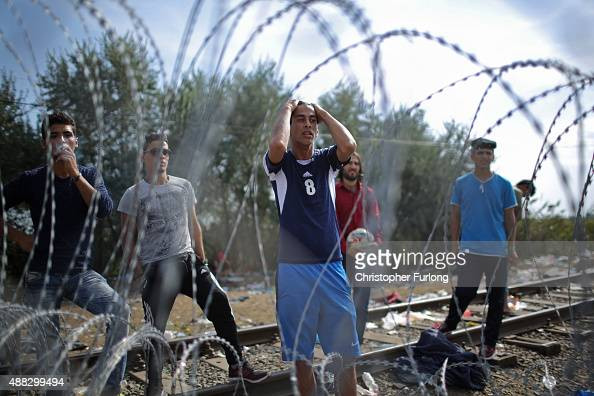 Migrants demonstrate with police officers through the razor wire fence from the Serbian side of the SerbianHungarian border at the closed rail track...