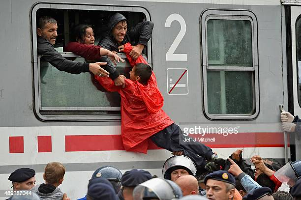 Migrants desperately try and board a train heading for Zagreb from Tovarnik station on September 20 2015 in TovarnikCroatia Croatia continues to send...