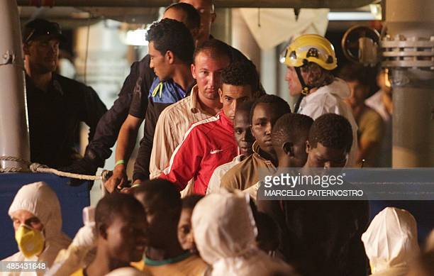 Migrants disembark from Swedish Coast Guards ship 'Poseidon' in the port of Palermo on August 27 2015 following a rescue operation in the...