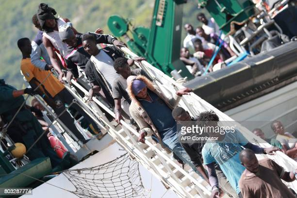 Migrants disembark from the Spanish Guardia Civil Rio Segura Patrol Ship with 1216 migrants onboard including 256 children and 11 pregnant women who...