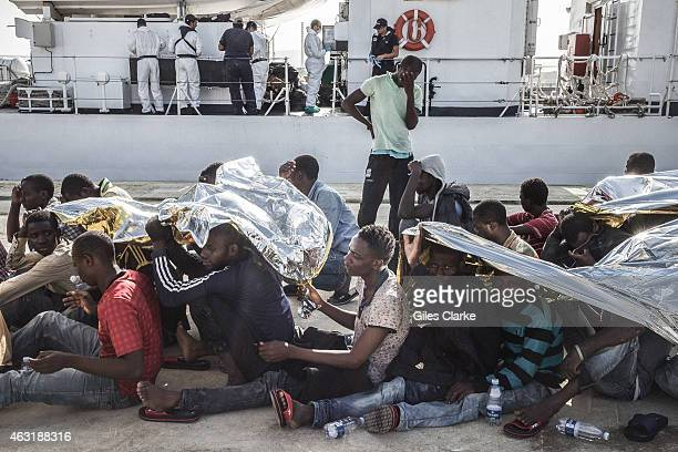 Migrants disembark the ship on October 15 2014 at the port of Augusta in Sicily and shield themselves from the midday sun Many have been at sea for...
