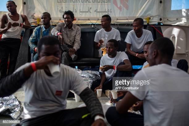 Migrants eat a meal on the deck of the Aquarius rescue ship run by NGO SOS Mediterranee and Medecins Sans Frontieres after the transfer from the NGO...