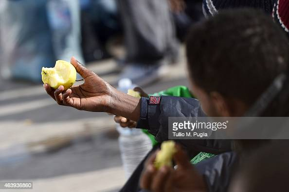 Migrants eat food as they wait to board a ship on February 20 2015 in Lampedusa Italy Hundreds of migrants recently arrived in Lampedusa after...