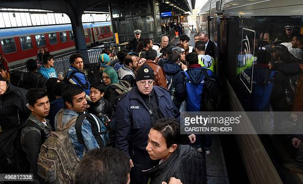 Migrants enter a train to Copenhagen Denmark on November 12 2015 at the railway station in Flensburg northern Germany where refugees in transit wait...